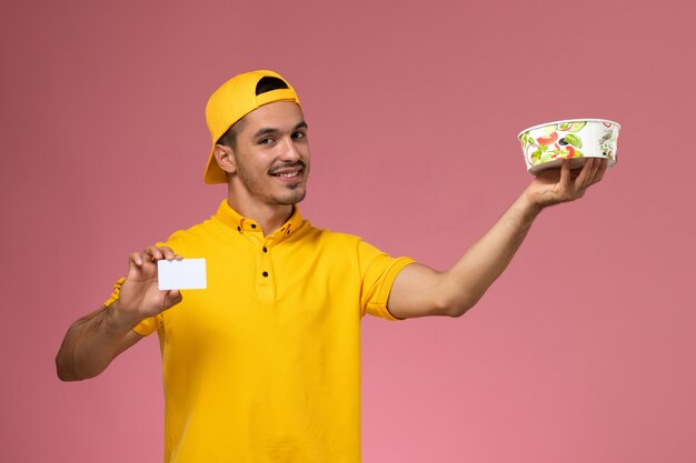 Vooraanzicht mannelijke koerier in de gele eenvormige kom van de holdingslevering met kaart op de roze achtergrond.