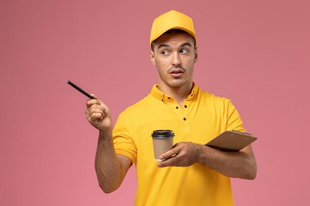 Vooraanzicht mannelijke koerier in geel uniform bedrijf levering koffiekopje en blocnote notities op lichtroze bureau opschrijven