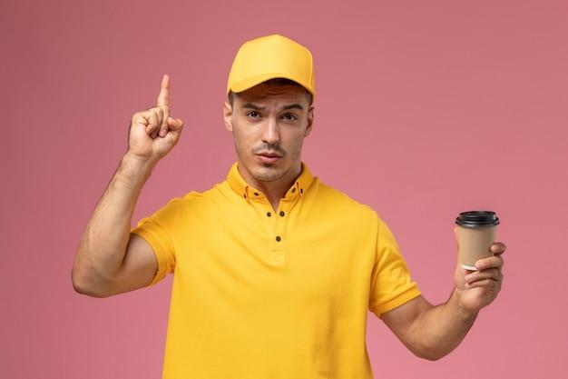Vooraanzicht mannelijke koerier in geel uniform bruin koffielevering kopje houden op de roze achtergrond