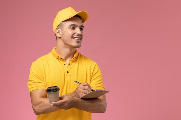 Vooraanzicht mannelijke koerier in geel uniform de koffiekop van de holdingslevering en blocnote het opschrijven van notities op het roze bureau