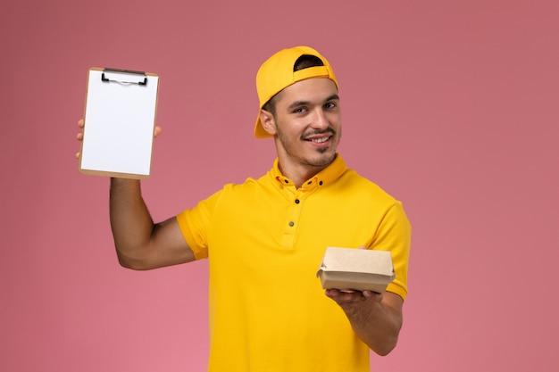 Vooraanzicht mannelijke koerier in geel uniform en cape die weinig notitieblok van het leveringsvoedselpakket op roze achtergrond houdt.