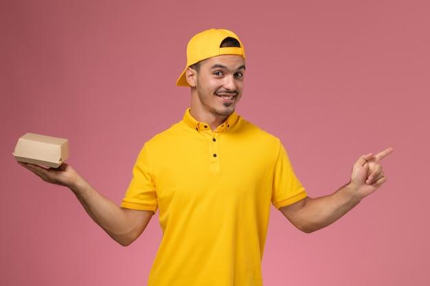 Vooraanzicht mannelijke koerier in geel uniform en cape die weinig pakket van het leveringsvoedsel houdt en op roze achtergrond glimlacht.