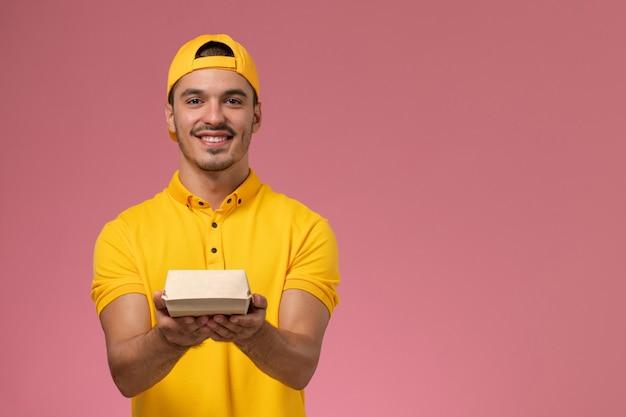 Vooraanzicht mannelijke koerier in geel uniform en cape die weinig pakket van het leveringsvoedsel op roze achtergrond houdt.