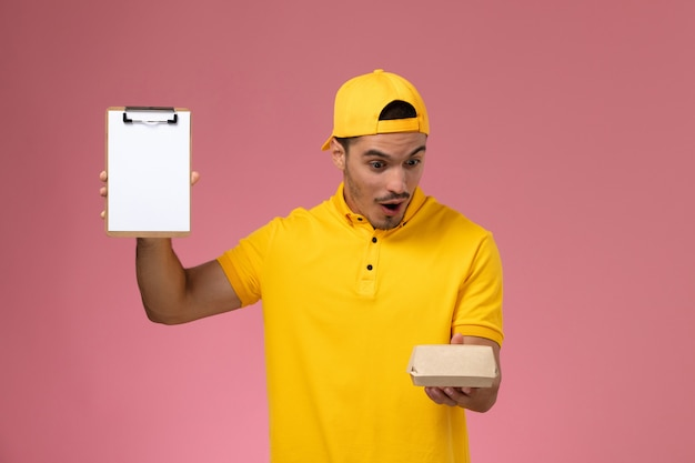 Vooraanzicht mannelijke koerier in geel uniform en cape die weinig voedselpakket en blocnote met verraste uitdrukking op roze achtergrond houdt.