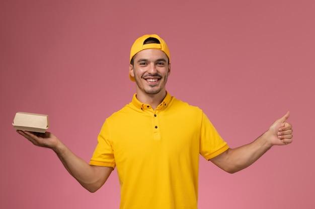 Vooraanzicht mannelijke koerier in geel uniform en cape die weinig voedselpakket houdt en op lichtroze achtergrond glimlacht.