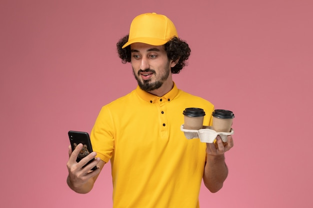 Vooraanzicht mannelijke koerier in geel uniform en cape met bruine bezorgkoffiekopjes en met behulp van een telefoon op roze muur