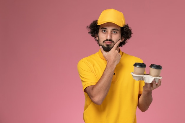 Vooraanzicht mannelijke koerier in geel uniform en cape met bruine levering koffiekopjes denken aan roze muur