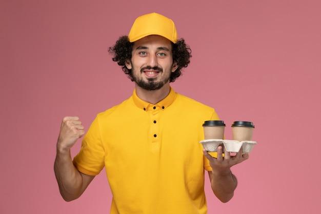 Vooraanzicht mannelijke koerier in geel uniform en cape met bruine levering koffiekopjes juichen op roze muur