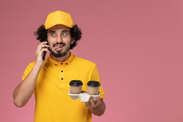 Vooraanzicht mannelijke koerier in geel uniform en cape met bruine levering koffiekopjes praten aan de telefoon op roze muur