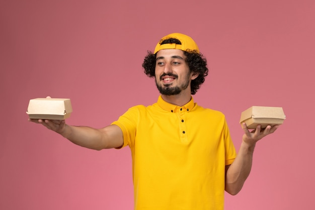 Vooraanzicht mannelijke koerier in geel uniform en cape met kleine bezorgvoedselpakketten op zijn handen lachend op de roze achtergrond.