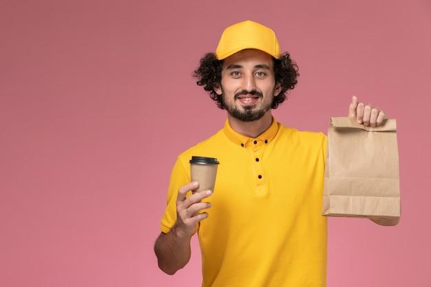 Vooraanzicht mannelijke koerier in geel uniform en cape met levering koffiekopje voedselpakket op de roze muur