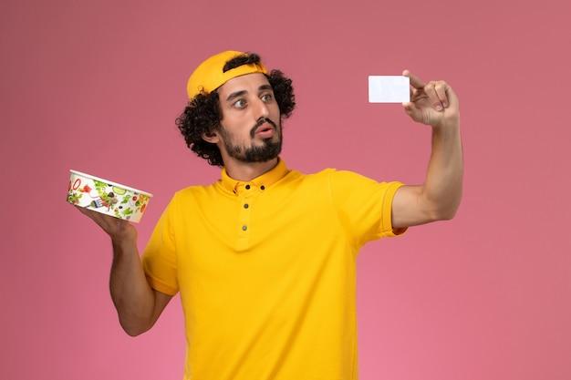 Vooraanzicht mannelijke koerier in geel uniform en cape met ronde leveringskom kaart op zijn handen op de roze achtergrond.