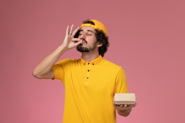 Vooraanzicht mannelijke koerier in geel uniform en cape met weinig bezorgvoedselpakket op zijn handen die zich voordeed op de roze achtergrond.