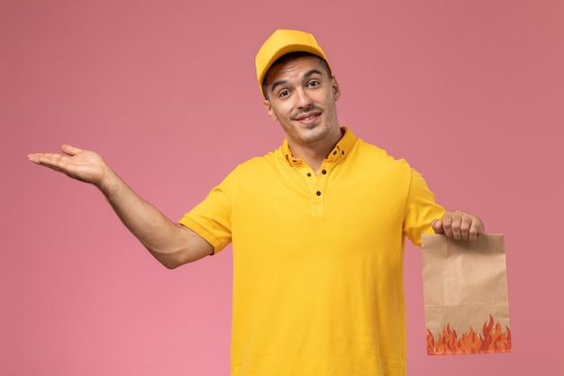 Vooraanzicht mannelijke koerier in geel uniform glimlachend en voedselpakket op de roze achtergrond te houden