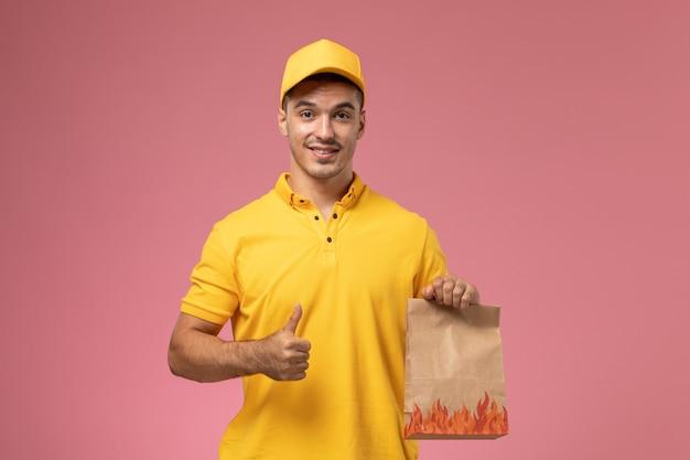 Vooraanzicht mannelijke koerier in geel uniform glimlachend en voedselpakket op het roze bureau te houden