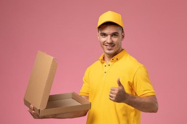 Vooraanzicht mannelijke koerier in geel uniform houden en openen van voedselleveringsdoos glimlachend op lichtroze achtergrond