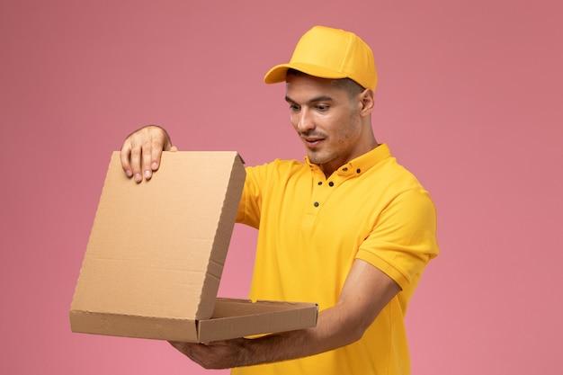 Vooraanzicht mannelijke koerier in geel uniform houden en openen van voedselleveringsdoos op roze achtergrond