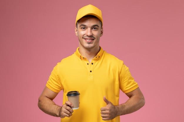 Vooraanzicht mannelijke koerier in geel uniform koffiekop houden en glimlachend op de roze achtergrond