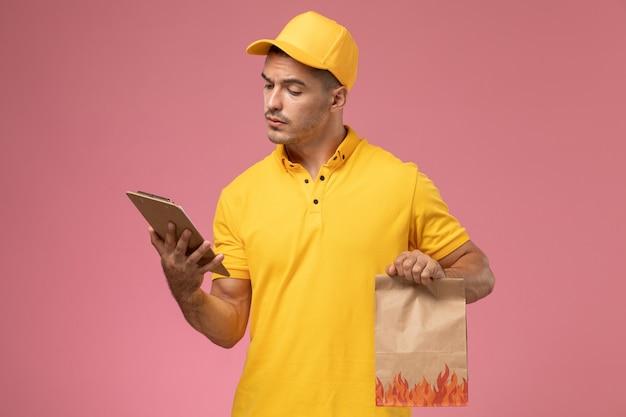 Vooraanzicht mannelijke koerier in geel uniform lezingsblok en voedselpakket op het roze bureau te houden