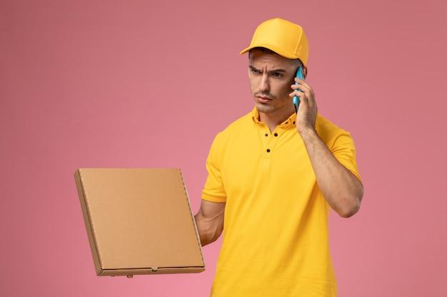 Vooraanzicht mannelijke koerier in geel uniform met behulp van telefoon praten en voedselleveringsdoos op het roze bureau te houden