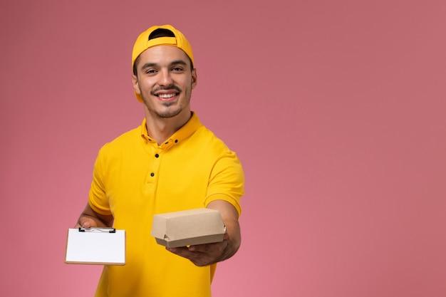 Vooraanzicht mannelijke koerier in geel uniform met blocnote en klein voedselpakket op de roze achtergrond.