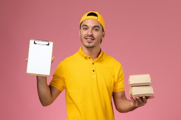 Vooraanzicht mannelijke koerier in geel uniform met kleine voedselpakketten op roze achtergrond.