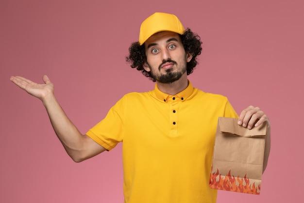 Vooraanzicht mannelijke koerier in geel uniform met papier voedselpakket op lichtroze muur