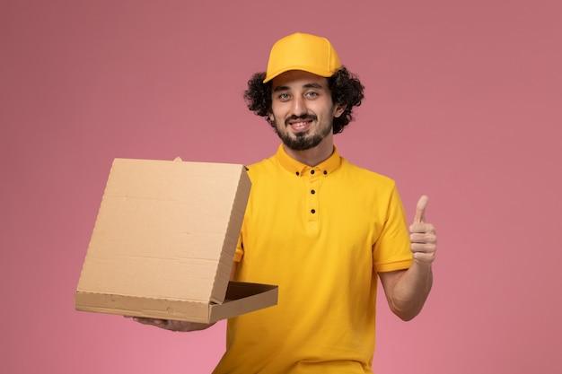 Vooraanzicht mannelijke koerier in geel uniform met voedselleveringsdoos lachend op de lichtroze muur