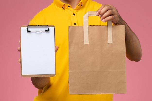 Vooraanzicht mannelijke koerier in geel uniform met weinig blocnote en bezorgvoedselpakket op de roze achtergrond.
