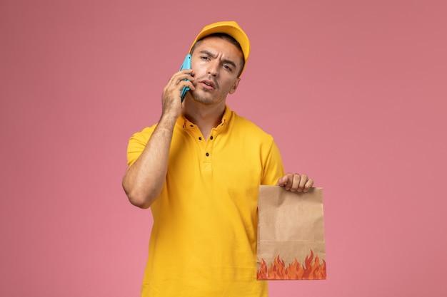 Vooraanzicht mannelijke koerier in geel uniform praten aan de telefoon met voedselpakket op roze