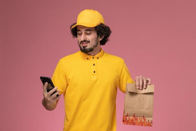 Vooraanzicht mannelijke koerier in geel uniform voedselpakket houden praten aan de telefoon op roze muur