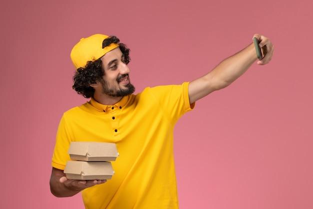Vooraanzicht mannelijke koerier in gele uniforme cape met voedselpakketten op zijn handen foto nemen op lichtroze achtergrond.