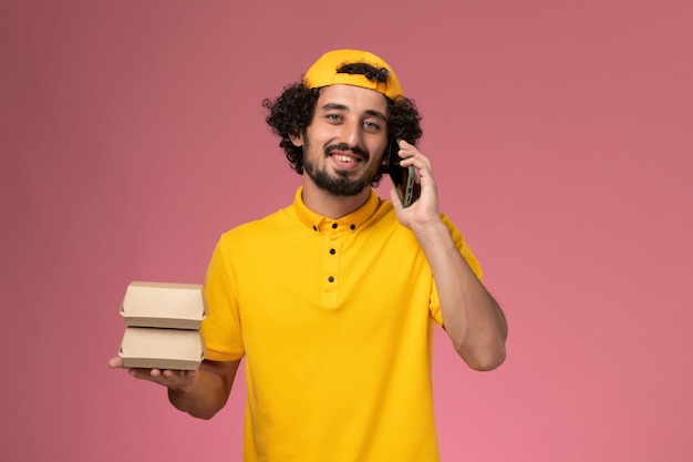 Vooraanzicht mannelijke koerier in gele uniforme cape met voedselpakketten op zijn handen praten aan de telefoon op lichtroze achtergrond.