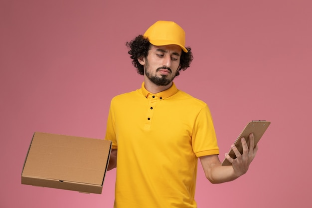 Vooraanzicht mannelijke koerier in gele uniforme de leveringsdoos van het holdingsvoedsel en blocnote die op roze muur denken