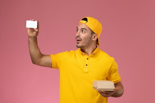 Vooraanzicht mannelijke koerier in gele uniforme holdingskaart en klein voedselpakket op roze achtergrond.