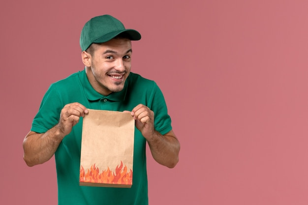 Vooraanzicht mannelijke koerier in groen uniform bedrijf papier voedselpakket met een glimlach op de roze achtergrond