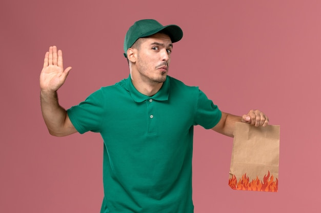 Vooraanzicht mannelijke koerier in groen uniform bedrijf papier voedselpakket op de lichtroze achtergrond