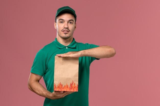 Vooraanzicht mannelijke koerier in groen uniform bedrijf papier voedselpakket poseren met het op lichtroze achtergrond
