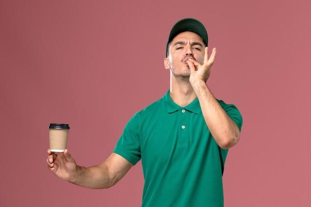 Vooraanzicht mannelijke koerier in groen uniform de koffiekop van de holdingslevering op lichtroze bureau