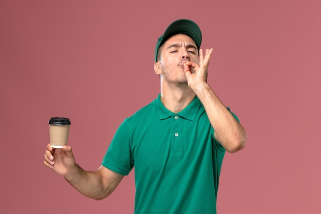 Vooraanzicht mannelijke koerier in groen uniform de koffiekop van de holdingslevering op roze bureau