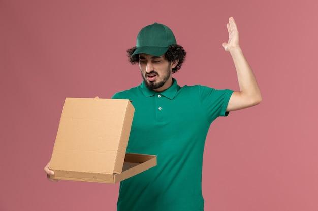 Vooraanzicht mannelijke koerier in groen uniform en cape die de doos van het leveringsvoedsel op roze de uniforme levering van de achtergronddienstmedewerker houden en openen