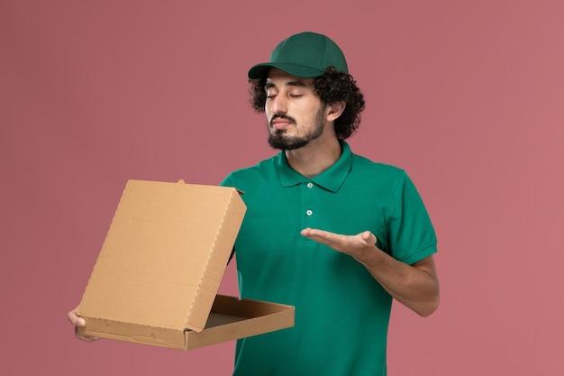 Vooraanzicht mannelijke koerier in groen uniform en cape die de doos van het leveringsvoedsel ruiken op roze achtergronddienst uniforme levering baan