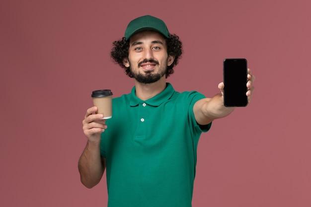 Vooraanzicht mannelijke koerier in groen uniform en cape levering koffiekopje met telefoon op roze achtergrond uniforme bezorgservice