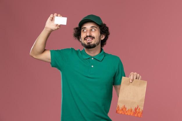 Vooraanzicht mannelijke koerier in groen uniform en cape met kaart en voedselpakket op de roze achtergrond service uniforme levering mannelijke baan werknemer werk