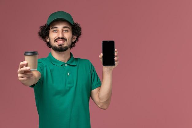 Vooraanzicht mannelijke koerier in groen uniform en cape met koffiekopje met telefoon op roze achtergrond uniforme levering baan service