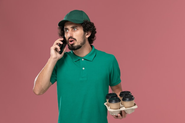 Vooraanzicht mannelijke koerier in groen uniform en cape met koffiekopjes en praten aan de telefoon op lichtroze achtergrond service uniforme levering mannelijke baan