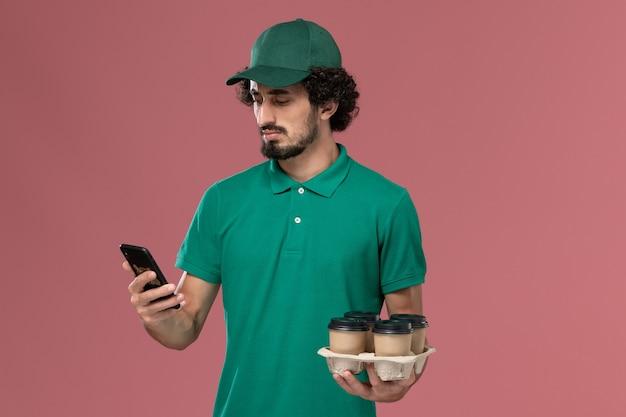Vooraanzicht mannelijke koerier in groen uniform en cape met koffiekopjes met behulp van zijn telefoon op de roze achtergrond service uniforme levering mannelijke baan