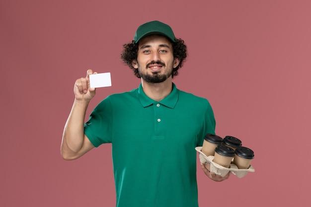 Vooraanzicht mannelijke koerier in groen uniform en cape met koffiekopjes met kaart op roze achtergrond service uniforme levering baan werknemer mannetje