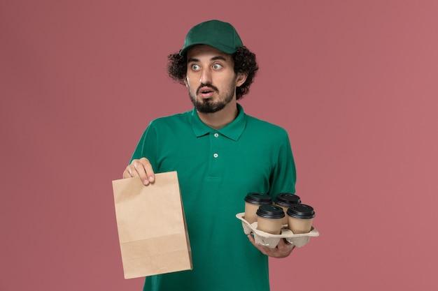 Vooraanzicht mannelijke koerier in groen uniform en cape met koffiekopjes met voedselpakket op roze achtergrond service uniforme levering baan werknemer mannetje