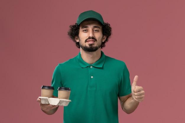 Vooraanzicht mannelijke koerier in groen uniform en cape met koffiekopjes op de roze achtergrond service uniforme levering baan werknemer